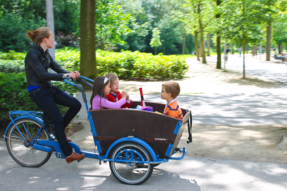 Young girl transporting children in the cart . Amsterdam. Netherlands