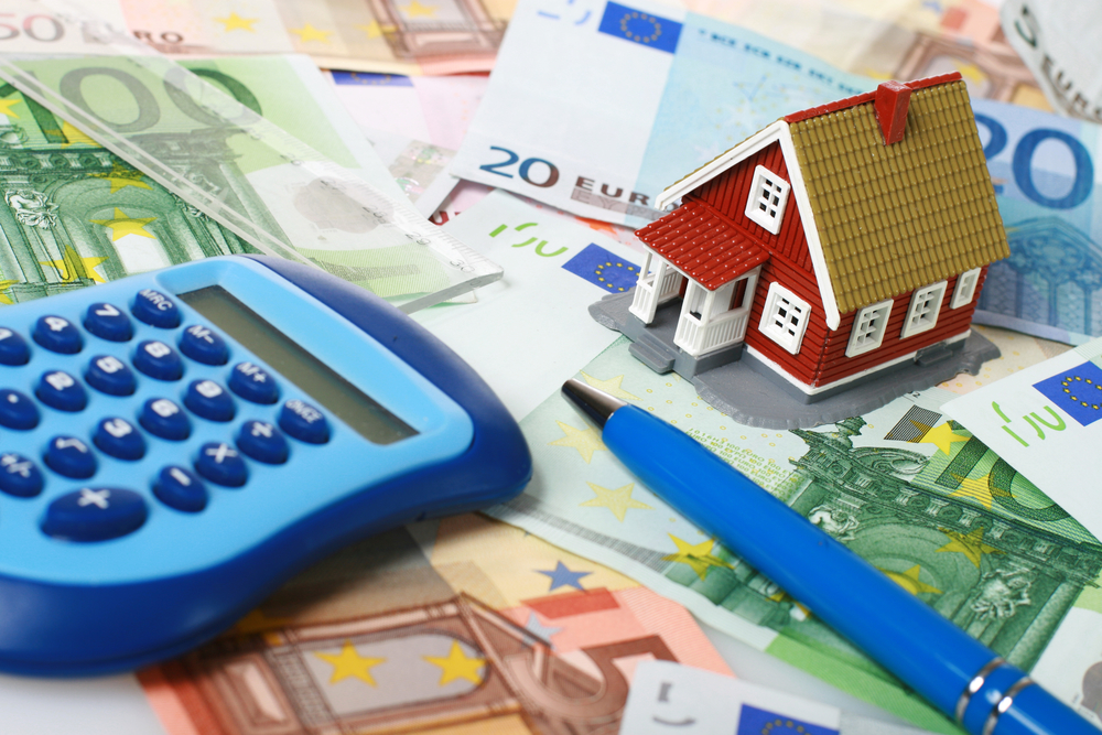 Small house, calculator and pen over euro money background.
